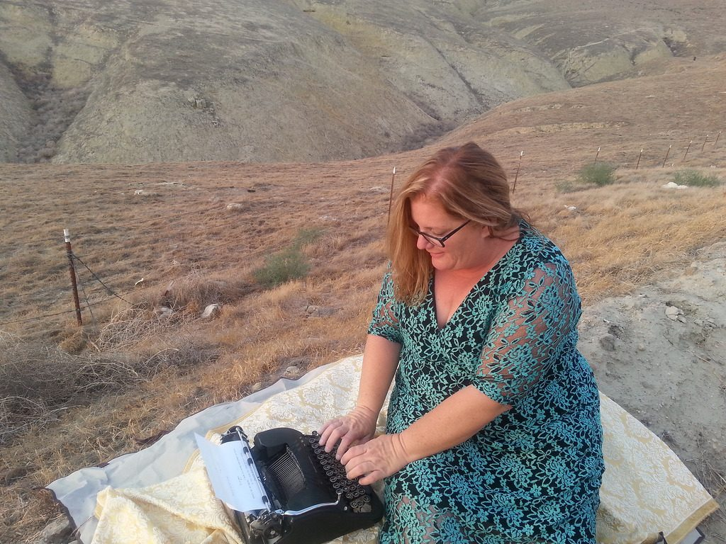 A women is typing in the countryside, another way of looking at a remnant of time and words, launching inspiration into the air.