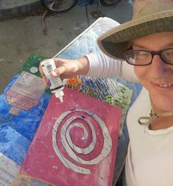 woman in a hiking hat creating mixed media art.