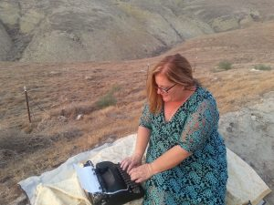 Julie JordanScott typing a love poem using a 1930's typewriter as she sits the edge of a foothill of the Sierra Nevada Mountains.