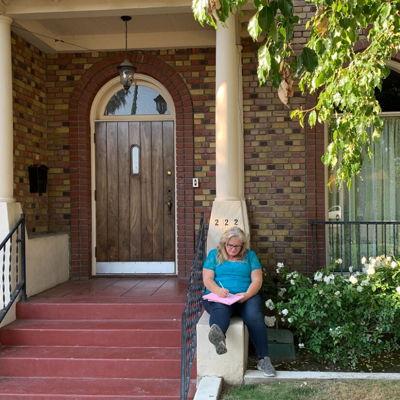Woman writing on the front porch of a brick home,