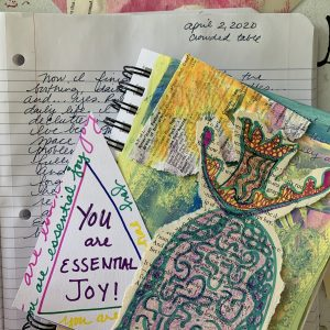 "A notebook on a table with an art journal with a variety of small paper works of art. One is a queenly figure, another is a triangle with a square that reads, ""You are essential joy"" from a poem by Hildegard de Bingen"