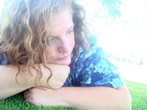 Woman in a funky mood looks contemplatively toward the side as she lies on a lawn, seeking solace.