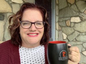 Julie Jordan Scott sits on her porch drinking coffee from a Lowell Observatory mug