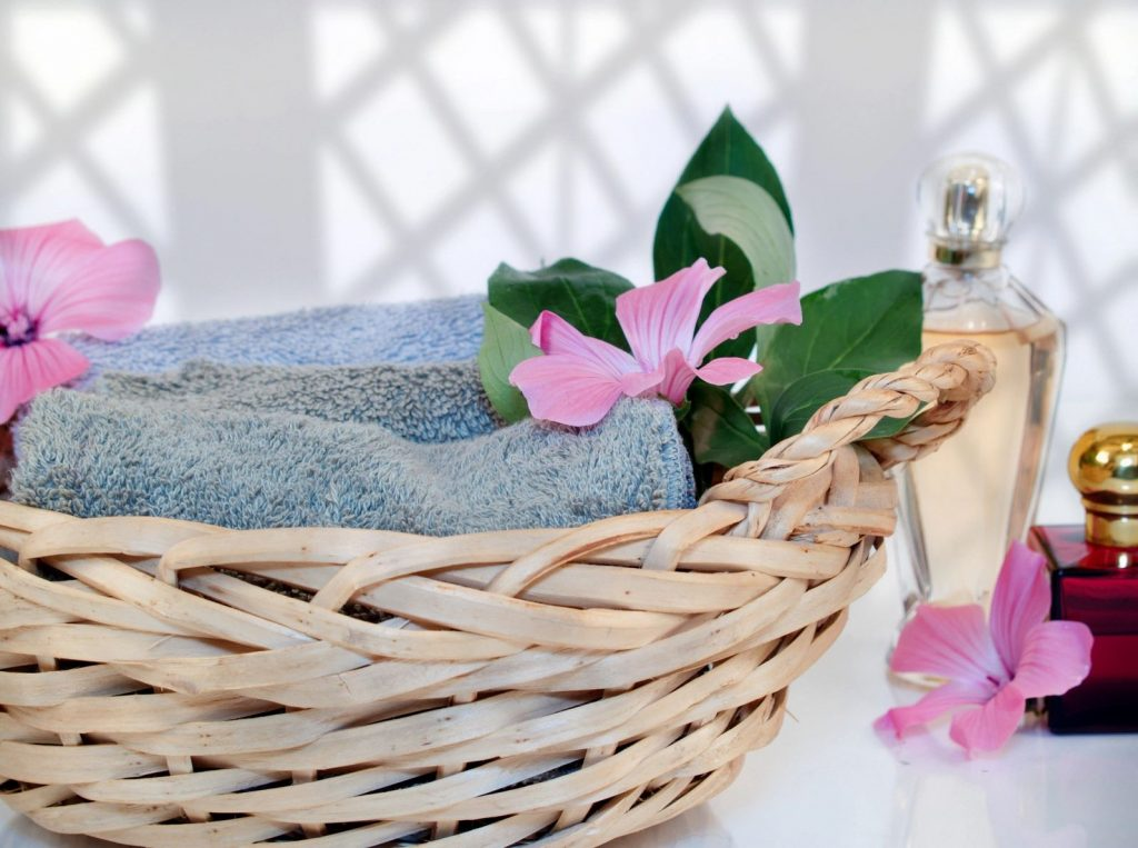 Basket of possibilities: a beige basket with towels and flowers, an image of self care