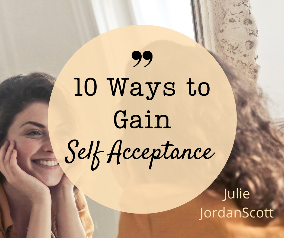 A woman looking in a mirror smiling at herself is a model of the article, 10 Ways to Gain Self Acceptance by Julie JordanScott