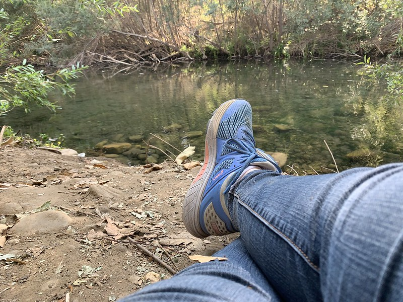 Woman's legs and shoes on the ground in front of a river. It is the writer of the blog, the Creative Life Midwife, practicing how to be a Warrior.